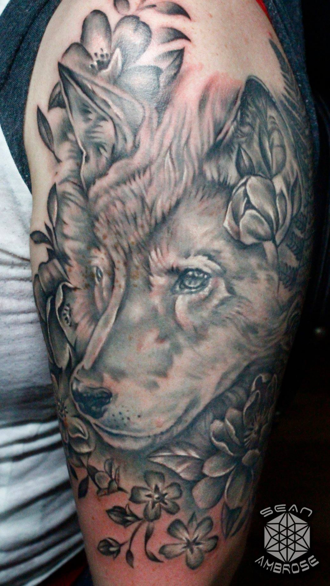 Custom realistic black and gray wolf tattoo by Sean Ambrose of Arrows and Embers Tattoo in Concord, New Hampshire (NH). Sean specializes in realism and surrealism custom Tattoos. He has been awarded as the Best Tattoo Artist in NH multiple years from multiple publications, and also won handfuls of awards for his tattoos and art.